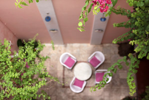 view bougainvillas courtyard patio canne furtniture coffee table reading book cow heads french colonial quarters design interiors Holy Chic Homes La Vie en Rose Pondicherry India agathe lazaro