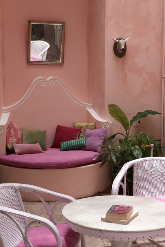 courtyard patio canne furtniture coffee table reading book cow heads french colonial quarters design interiors Holy Chic Homes La Vie en Rose Pondicherry India agathe lazaro
