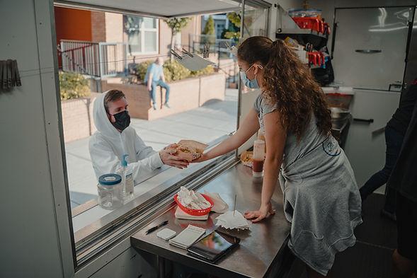 Food truck employee serving customer
