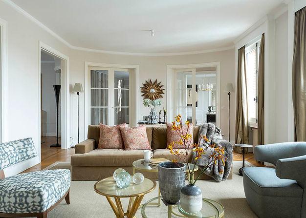salon avec un grand canapé beige, avec une table basse et 2 fauteuils en premier plan