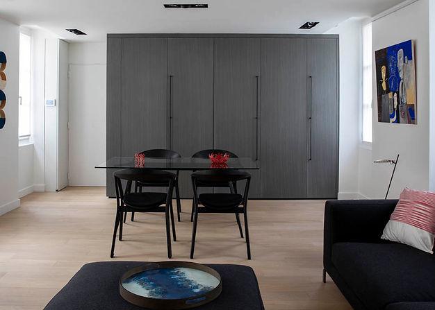 Grand placard en bois gris avec une table en verre devant. un canapé noir à droite et un parquet clair