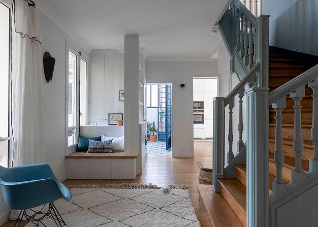 un tapis au sol et un esclier bleu sur la droite. 2 ouvertures donne sur une entrée et une cuisine.