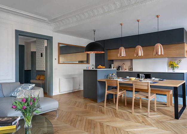 cuisine ouverte de couleur bleue avec un ilot central qui sert de table à manger. du parquet au sol