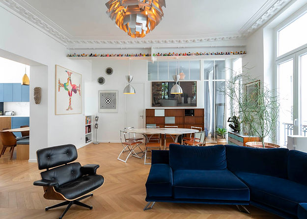 Salon avec un canapé en velour bleu. une table et des chaises sont en arrière plan