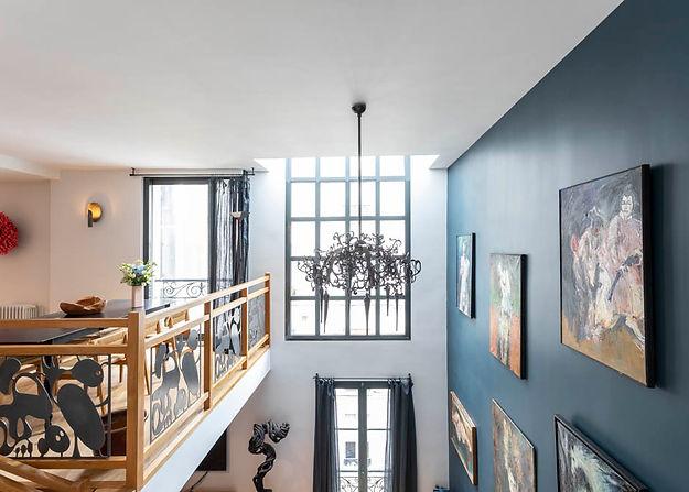 Grande fenêtre avec à sa droite un mur bleu et à sa gauche une mezzanine