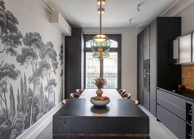 cuisine noire et blanche avec ilot cental. A gauche un mur en papier peint et à droite des éléments de cuisine