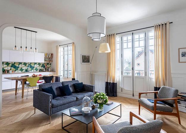 Salon ouvert sur cuisine. un canapé et 2 fauteuils gris entourent une table basse en métal noir.