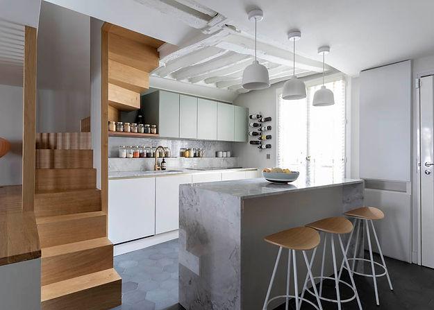 cuiisne ouverte avec un ilot central. un escalier en bois sur la gauche