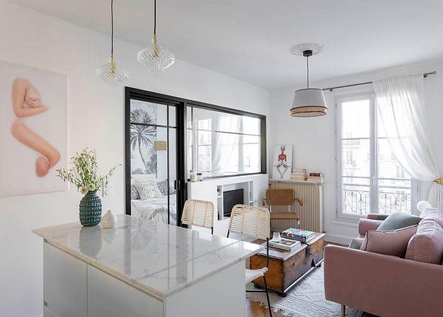 salon avec canapé rose et table basse en bois. la chambre se situe derrière une verrirère