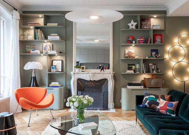 Une cheminée en marbre blanc est entourée d'étagère de couleur kaki. il y a devant une table basse en verre entourée d'un canapé en velour et d'un fauteui orange