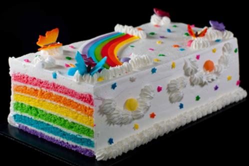 Layers of horizontal vanilla sponge of rainbow colors and orange cream icing