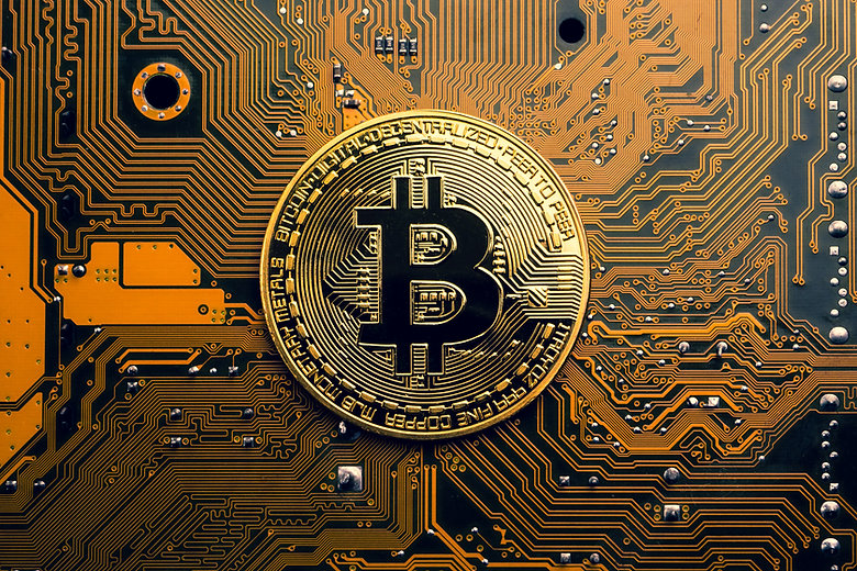 A golden coin with bitcoin symbol on a mainboard..jpg