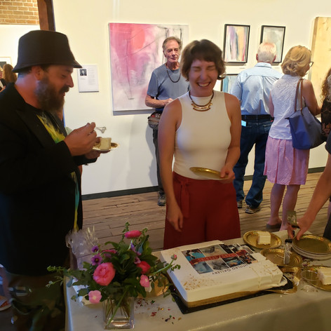 Artists, Inna Rohr and Jessie Shinn cutting the cake, and having a laugh.