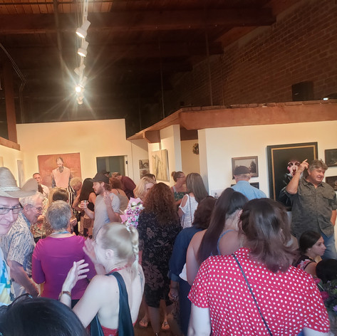 Artists, guests, and collectors fill the space.
