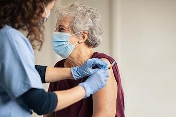 elderly_woman_receiving_covid_vaccine_-_