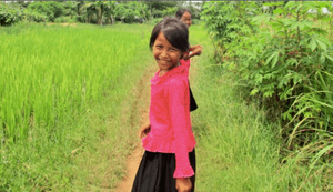 Image of a Cambodian girl on a village path through a field looking back at the camera and smiling. It's an image from Free To Shine, a child protection agency in Cambodia that protects young girls from sex traffickers by keeping them in school.