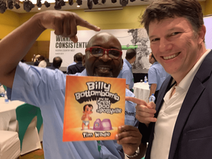 The participant who received one of Tim's children's books during a funny element on stage, poses with his prize and it's author!