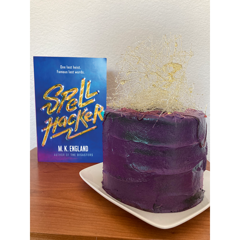 A cake with shiny purple frosting and spun sugar decorations sits on a table next to the book Spellhacker.