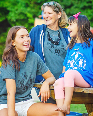 Two smiling volunteers and one smiling camper in blue camp t-shirts