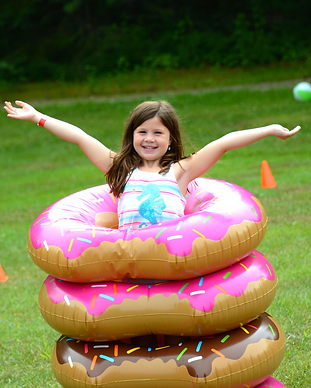 Smiling kid standing in 3 inflatable donuts with arms raised to the side