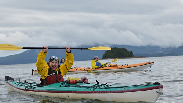 Smiling Breaking Borders participant in a sea kayak holding the paddle above their head
