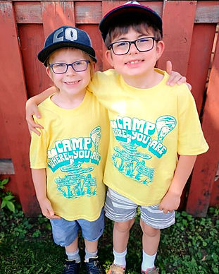 Two smiling kids with glasses and hats in Camp Quality t-shirts