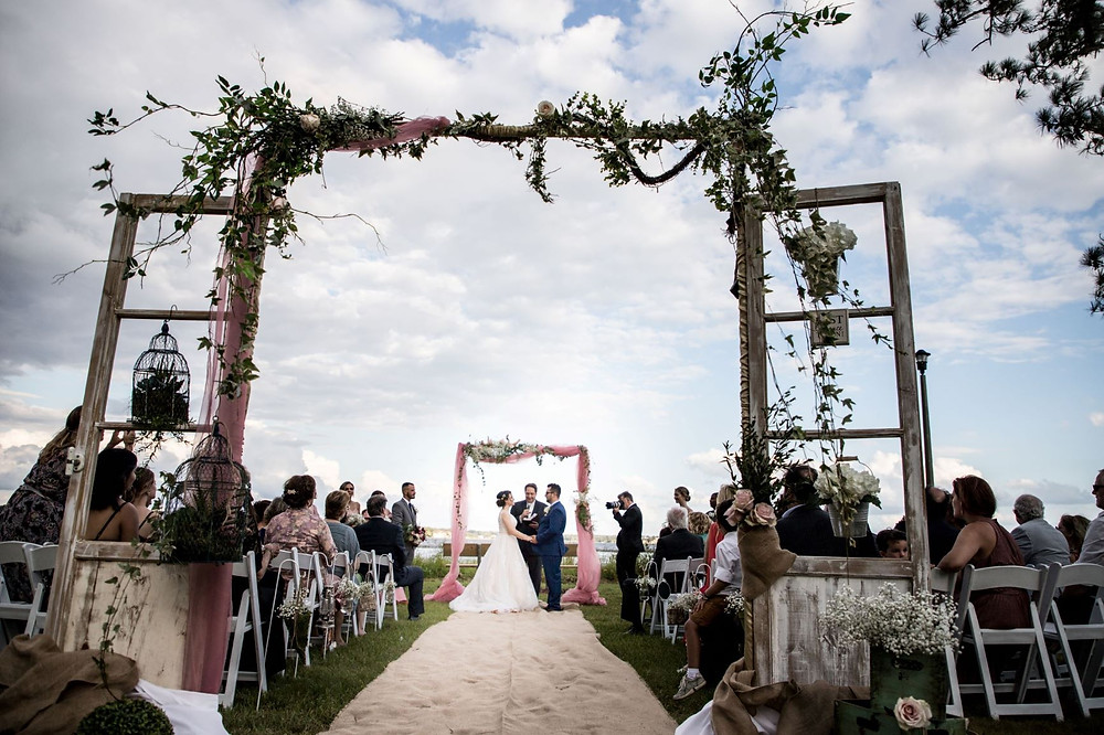 Outdoor ceremony with french doors and floral.