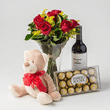 Arranjo com 7 rosas carollas no vidro chocolate,vinho e pelúcia
