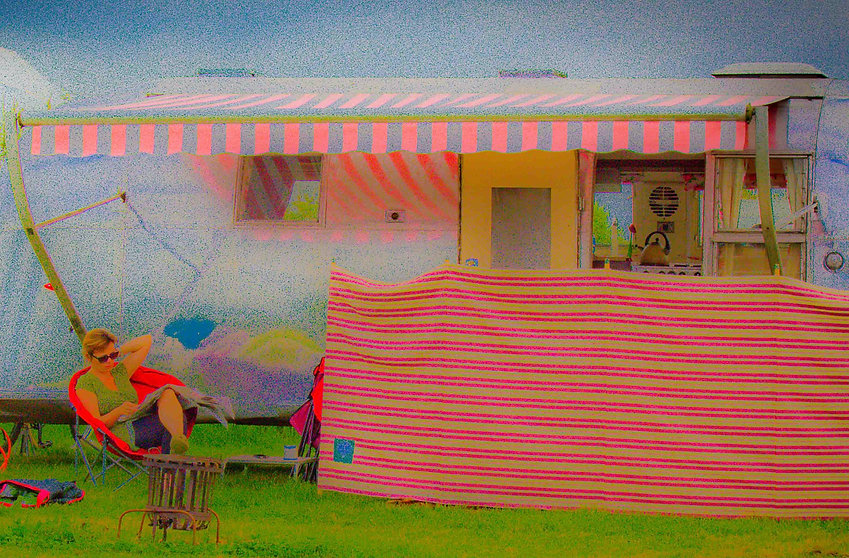 Airstream Hire UK - Picture of lady relaxing by reading paper in front of an Airstream Trailer at a Festival