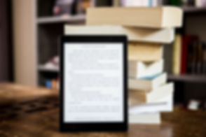 black-tablet-computer-behind-books-13295