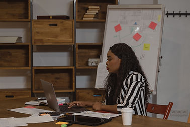 A young black woman sits at a desk with a laptop and lots of papers. Behind her is a white board with planning diagrams and post-its.