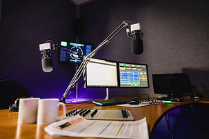 A front view shot of a radio station studio interior, a large desk is in the middle of the