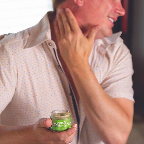 man using cbd & me balm on his sore neck