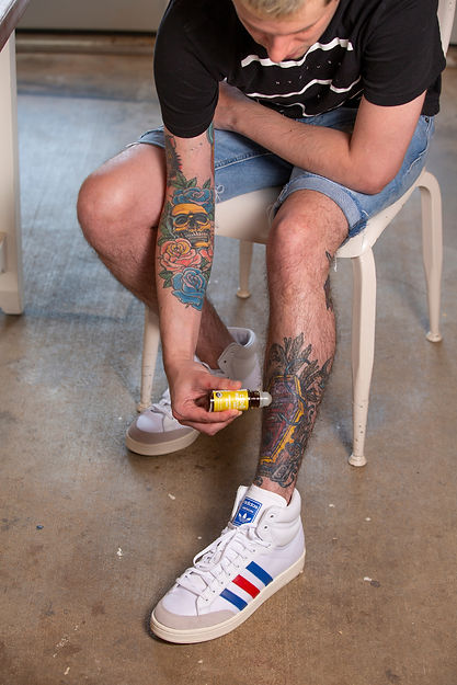 man using CBD & ME roller on his sore leg