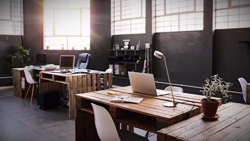 Diseño de oficinas con sala de mesas altas para trabajo compartido