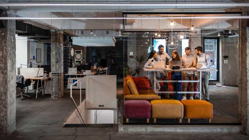 Oficina moderna des estilo industrial con espacios abiertos y mamparas de cristal.