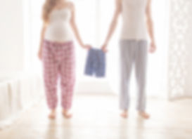 pregnant couple holding children's pajam