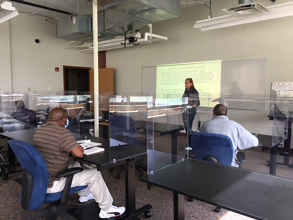 Woman stands behind a plexiglass screen in front of a classroom in front of adult learners for workforce manufacturing. All learners are behind individual plexiglass screens.