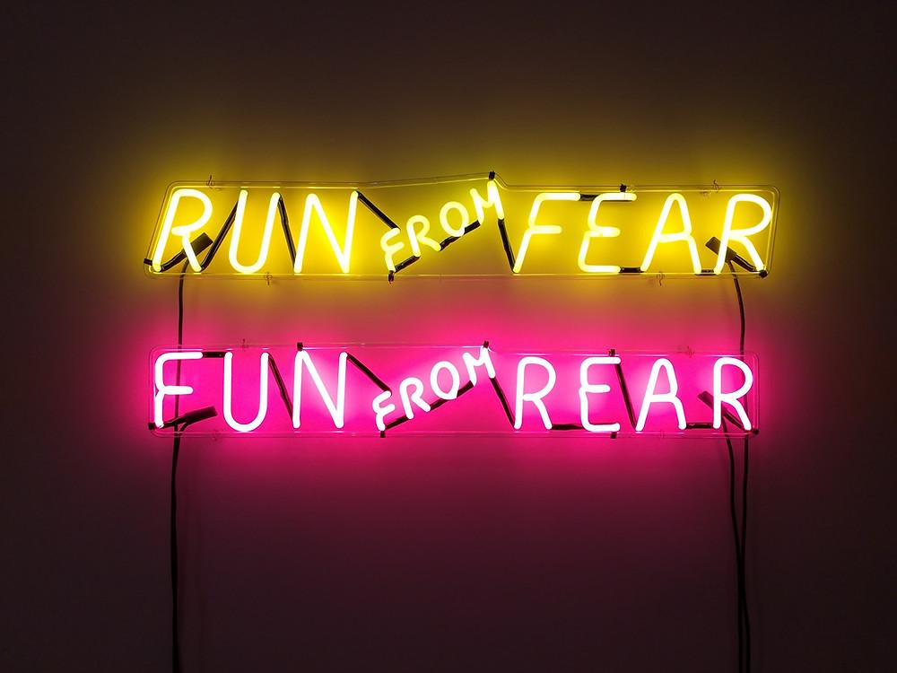 """Neonschriftzüge """"Run from fear, fun from rear"""""""