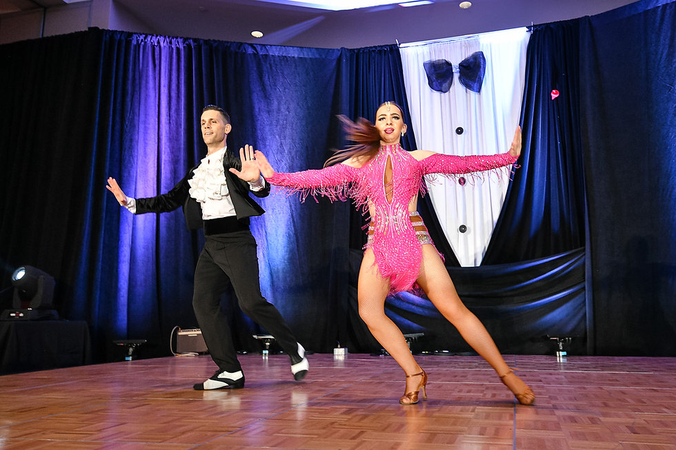 Couple performing Salsa on stage with classy costumes