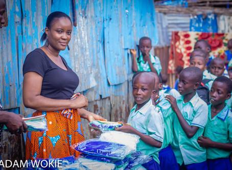Madam Wokie presents uniforms to pupils of the Kroo Bay Community School, Freetown