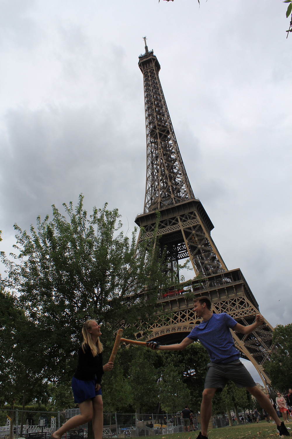 Corrine and her friend in front of the Eiffel Tower in Paris, France having a baguette fight