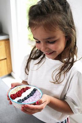 meisje houdt yoghurt toetje met paars fr