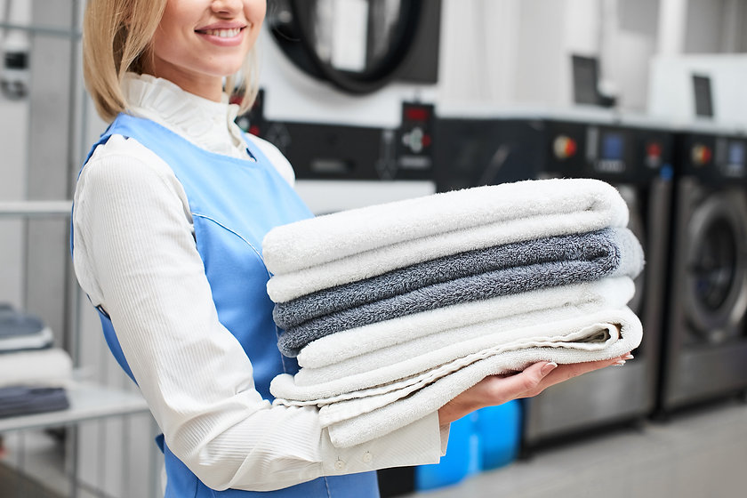 Worker Laundry girl holding fresh towels in her hands and smiles at the dry cleaners