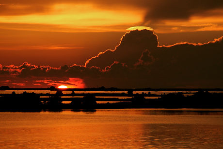 Sunset Over Water With Billowing Clouds.