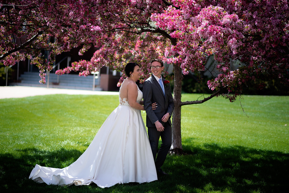 bride & groom have first look near student union on UNL Campus in Lincoln, Nebraska during Spring blooms.