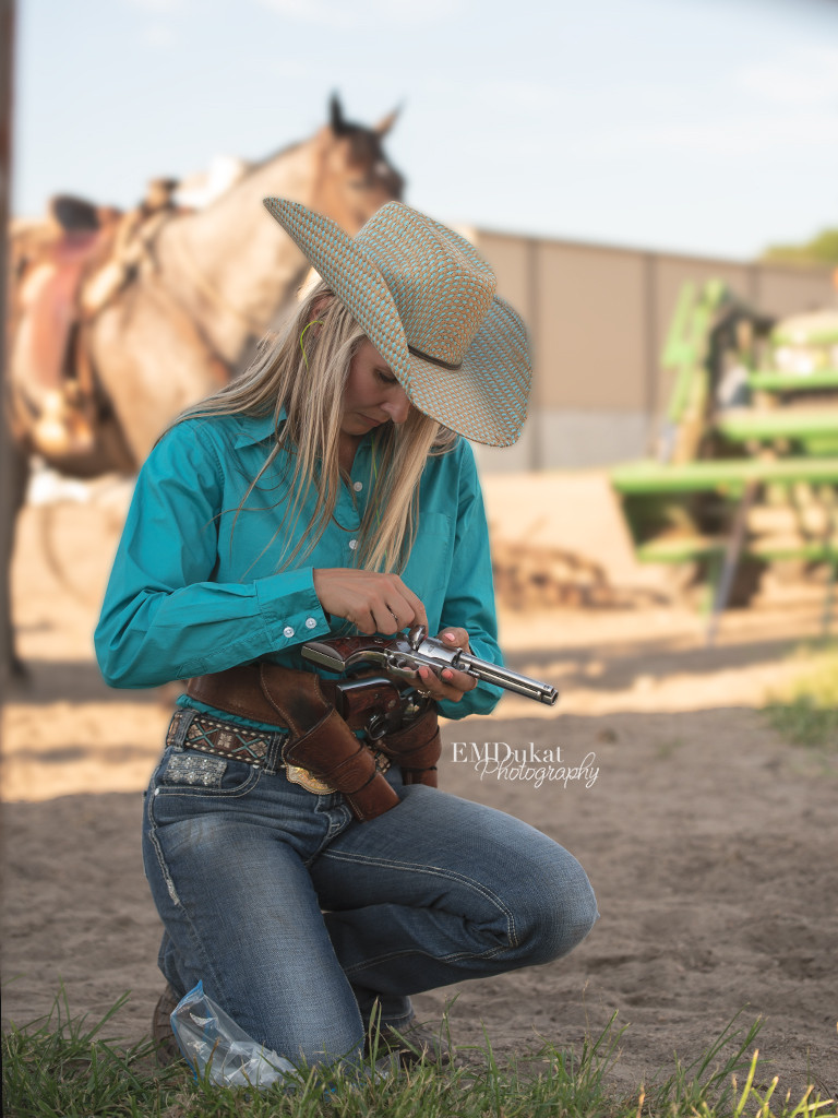 cowgirl loading her gun at mounted shooting event in Elkhorn, NE