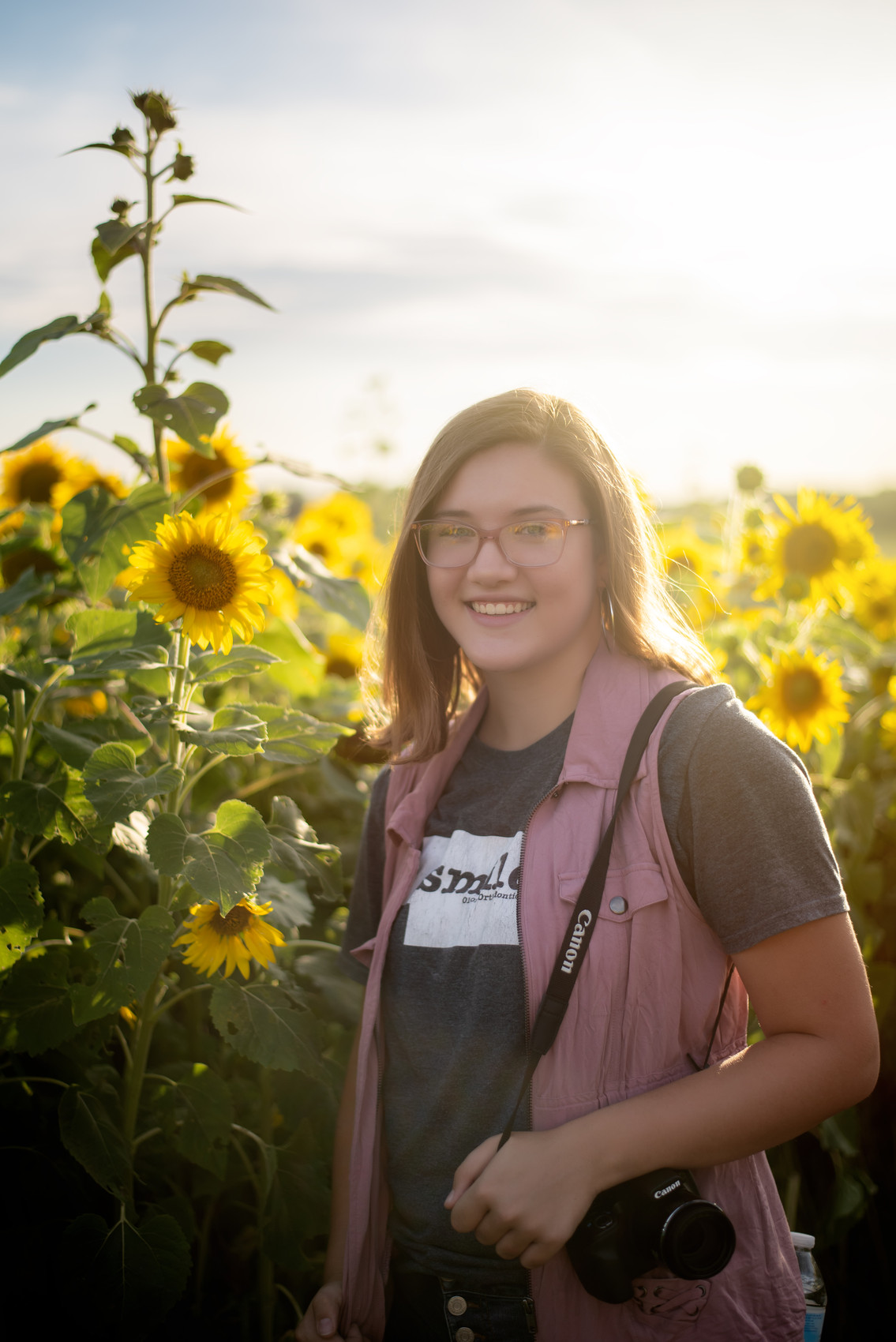 teen smiling and posing in sunflower field at Nelson Produce in Valley, Nebraska