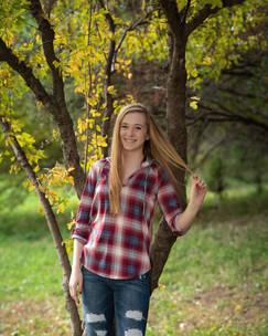 senior girl leans against tree in Gretna, Nebraska