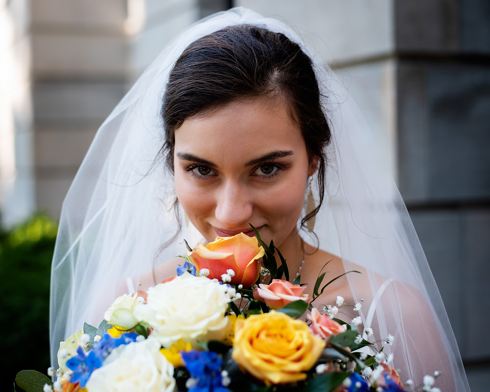 bride grins behind her beautiful, bold bouquet